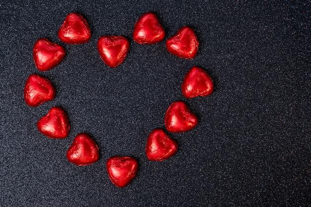 Конфеты в форме сердца в красной фольге на черном фоне с блестками