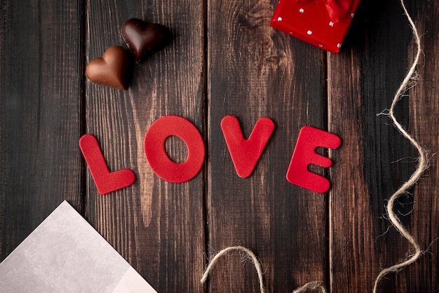 Heart-shaped chocolates on wooden background with love