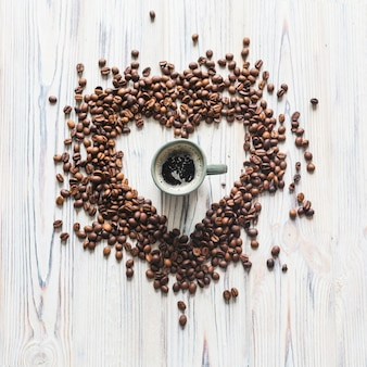 Heart shaped coffee beans around coffee cup
