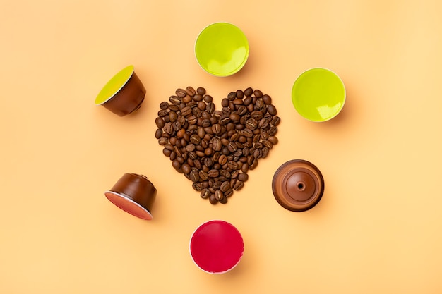Heart shaped coffee beans and capsules around on beige