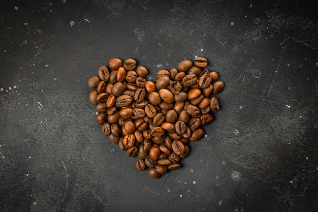 Heart shaped coffee beans on dark gray background, coffee love concept.