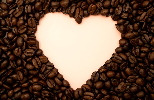 Heart shaped coffee beans on pink
