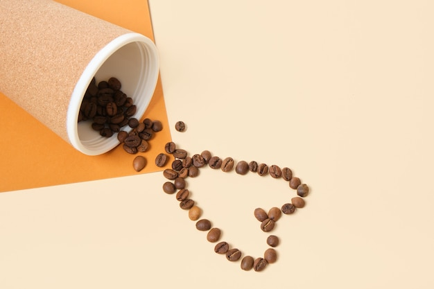 Heart shaped coffee beans sprinkled from reusable thermo mug covered with cork, beige and brown geometric background copy space