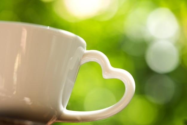 보케 자연 배경에 하트 모양의 커피 컵 손잡이.