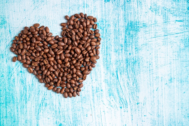 Heart shaped coffee grains on aquamarine background