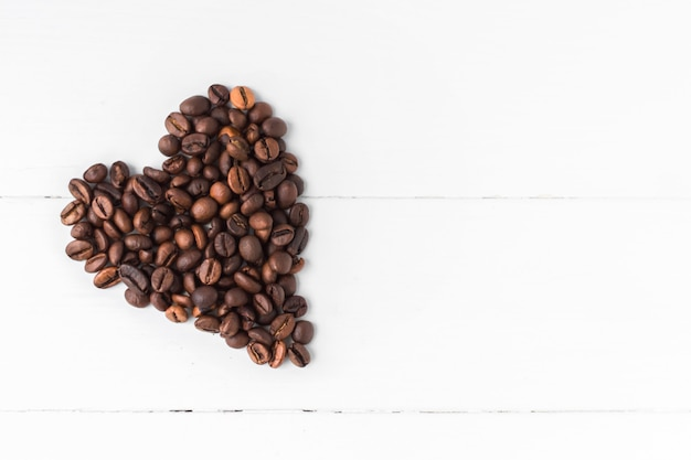Heart-shaped coffee grains on white wooden background