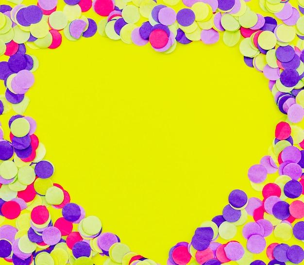 ハート形の黄色の背景にカラフルな紙吹雪