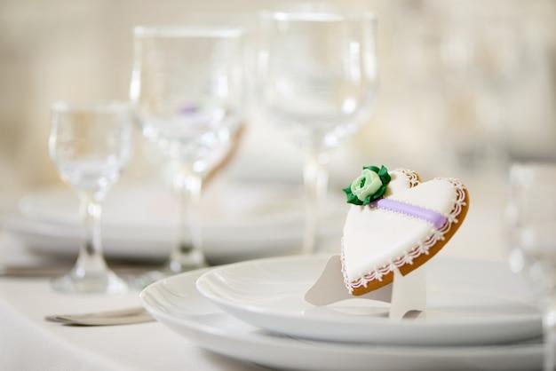 Печенье в форме сердца, покрытое сладкой глазурью, украшенное зеленым цветком и мелким узором, стоит на белых тарелках в качестве украшения праздничного свадебного стола возле бокалов для вина.