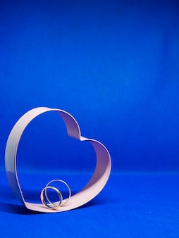 Heart-shaped cookie mold frame. in the center wedding rings. blue background, isolated, copy space for message. valentine's day concept declaration of love.