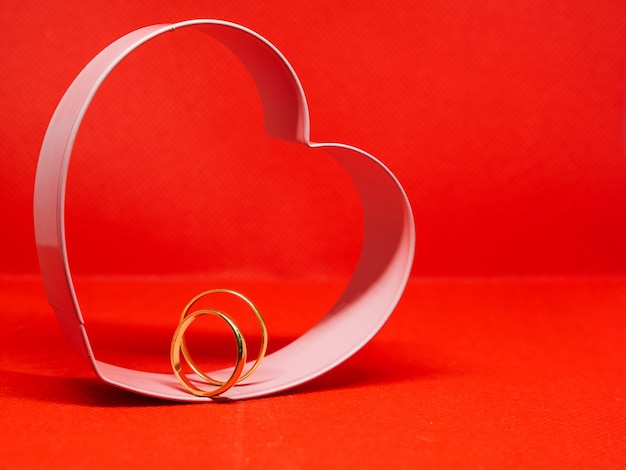 Heart-shaped cookie mold frame. in the center wedding rings. red background, isolated, copy space for message. valentine's day concept declaration of love.