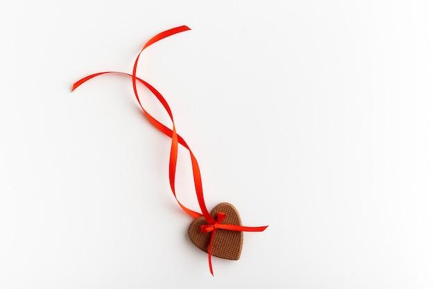 Печенье в форме сердца с красной лентой на белой поверхности. день святого валентина.