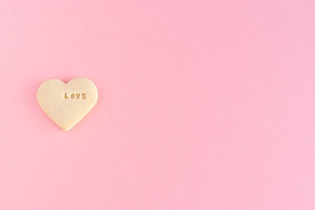 Печенье в форме сердца со словом любовь на розовом фоне день святого валентина, день матери, годовщина. скопируйте пространство. вид сверху.