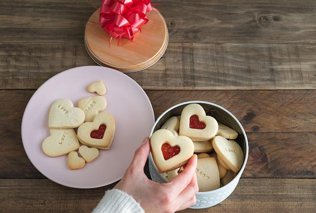 Печенье в форме сердца с вареньем. коробка печенья заполнения руки женщины.