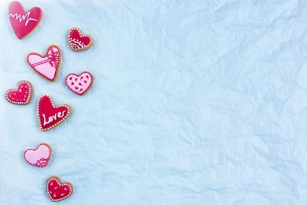 Плоское печенье в форме сердца на день святого валентина со знаком любви. фото высокого качества