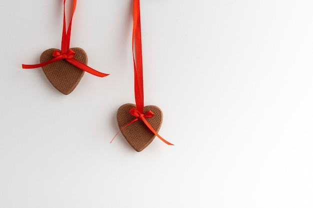 ハート型のクッキーは、赤いリボン、白い背景に掛かっています。バレンタインデーの装飾。スペースをコピーします。