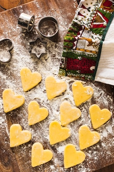 Heart-shaped cookies near towel and cutters