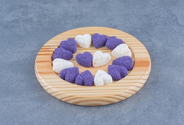 大理石の背景に、プレート上のハート型のクッキー。