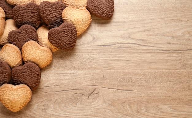 심장 모양의 나무 배경에 쿠키. 구운 버터와 초콜릿 쿠키, 텍스트에 대 한 빈 공간. 발렌타인 데이