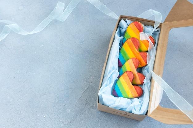 Печенье в форме сердца, раскрашенное радужным флагом лгбт, в подарочной коробке.