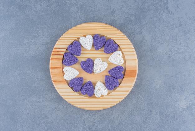 Biscotti a forma di cuore sul piatto, sullo sfondo di marmo.