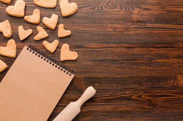 Heart-shaped cookies for valentines day with notebook and rolling pin