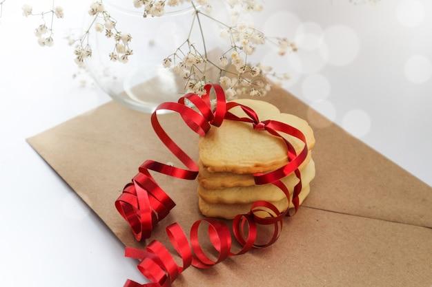 빨간 리본과 꽃의 흰색 부케와 하트 모양의 쿠키.