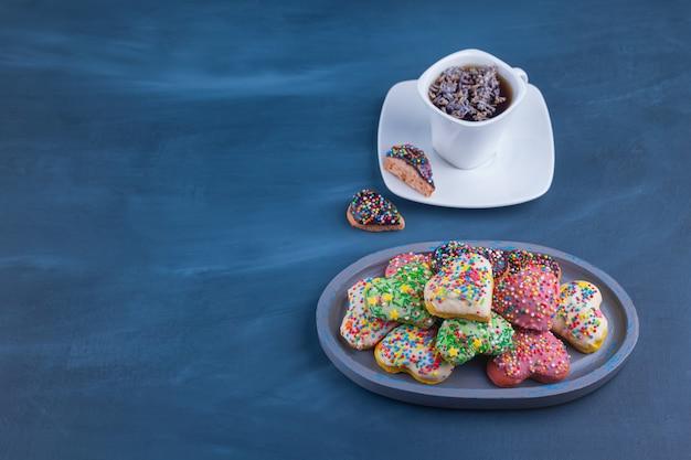 カラフルなスプリンクルと紅茶のカップが付いたハート型のクッキー。