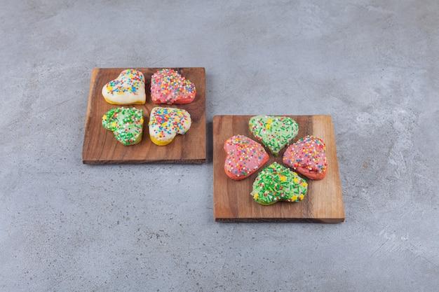 木の板の上にカラフルな振りかけるハート型のクッキー。