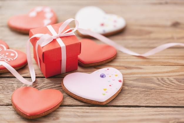 Печенье в форме сердца с подарочной коробкой на день святого валентина или день матери на деревянных фоне.