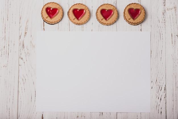Biscotti a forma di cuore su un tavolo di legno con un foglio bianco