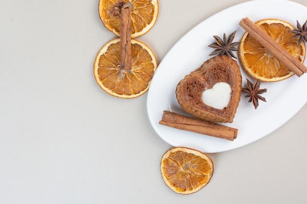 白いプレートにオレンジスライス、クローブ、シナモンとハート型のクリーミーなケーキ