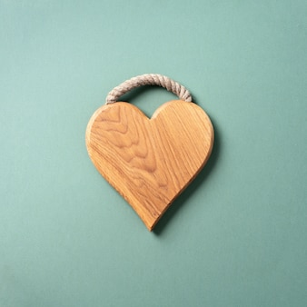 Heart shaped cutting board over blue and green background.