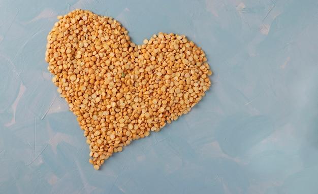 Сушеные зерна гороха в форме сердца на светло-голубой поверхности, крупным планом, копией пространства
