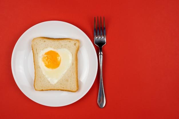 白いセラミックプレート上のトーストしたライ麦パンのスライスのハート型の卵。バレンタインデーのコンセプト。朝食のデザインが大好きです。自家製ヘルシーサンドイッチ。お祝いのランチまたは朝食。スペースをコピーします。