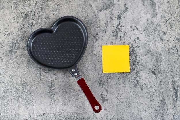 Пустая сковорода в форме сердца с желтой наклейкой на камне.