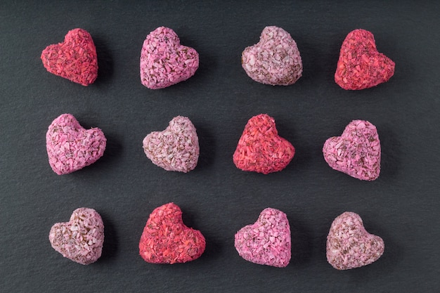 Heart shaped energy bites for valentine's day on slate plate, flat lay