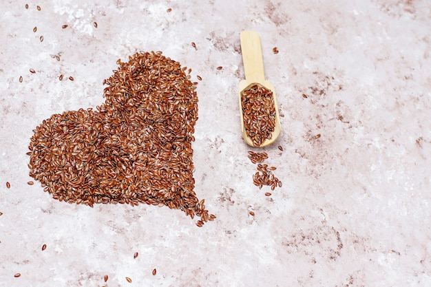 Heart shaped flax seeds on concrete background with space for copy,top view