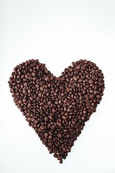 白い背景で隔離のハート型の新鮮な香りのコーヒー豆コピースペース