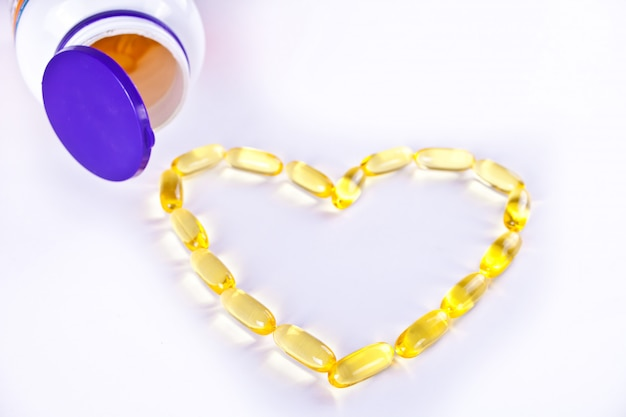 Heart shaped gel capsules with bottle. medical, pharmacy and healthcare concept. copy space.