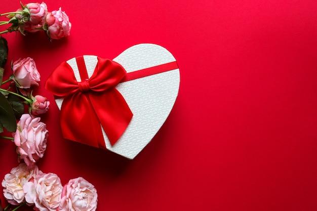 ハート型のギフトボックスとコピースペースのある赤い背景にバラの花。バレンタインデーのコンセプト
