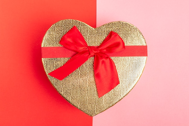 Heart shaped gift box with ribbon bow on pink, red background top view