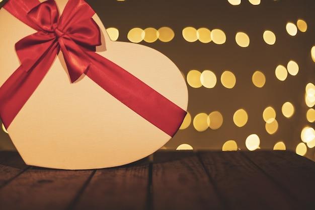 Confezione regalo a forma di cuore su un tavolo di legno con uno sfondo bokeh