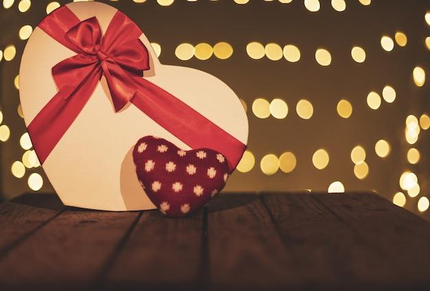 Scatola regalo a forma di cuore su un tavolo di legno con uno sfondo bokeh di fondo