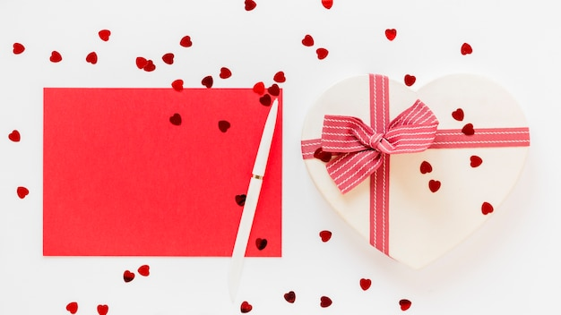 Heart-shaped gift with pen and paper for valentines