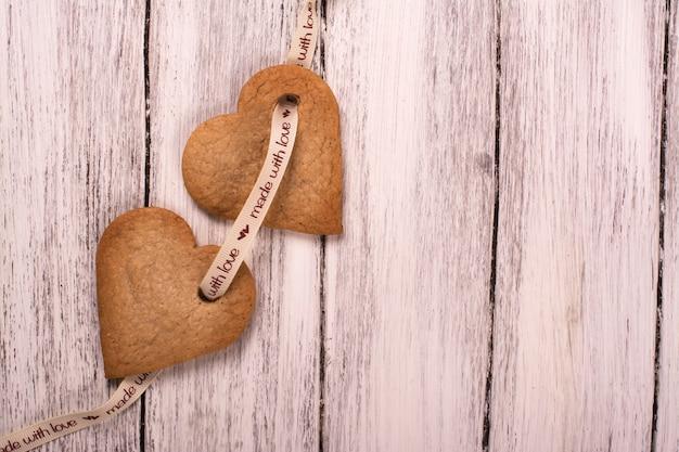 Имбирное печенье в форме сердца на белом фоне деревянные Premium Фотографии