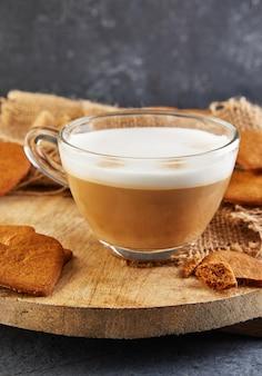 木の板にカプチーノコーヒーを入れたハート型のジンジャーブレッドクッキー。