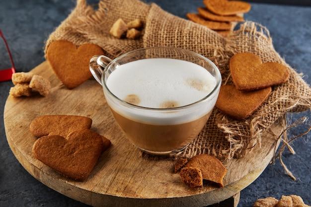심장 모양의 나무 보드에 카푸치노 커피 한잔과 함께 진저 쿠키.