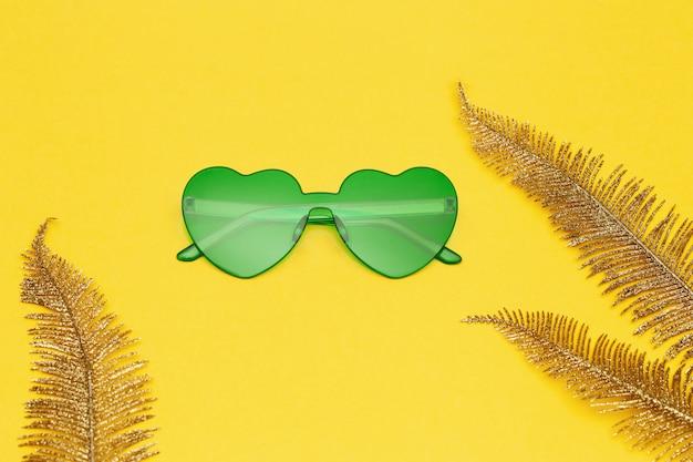 Очки в форме сердца и золотые пальмовые листья на желтой бумаге