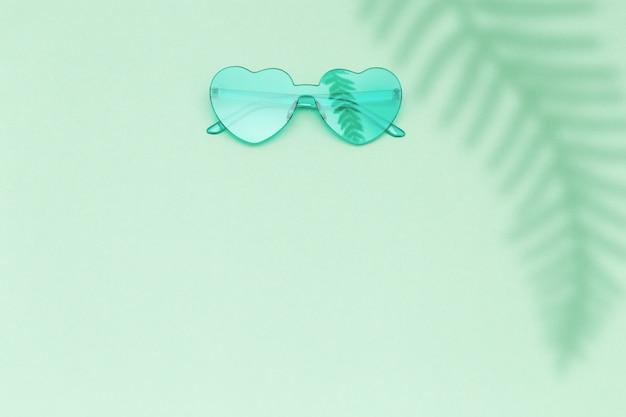 심장 모양의 그림자와 종이 표면에 녹색 안경 프리미엄 사진