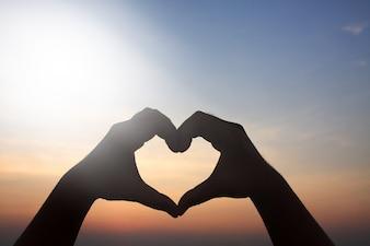 Heart-shaped hand, sky background